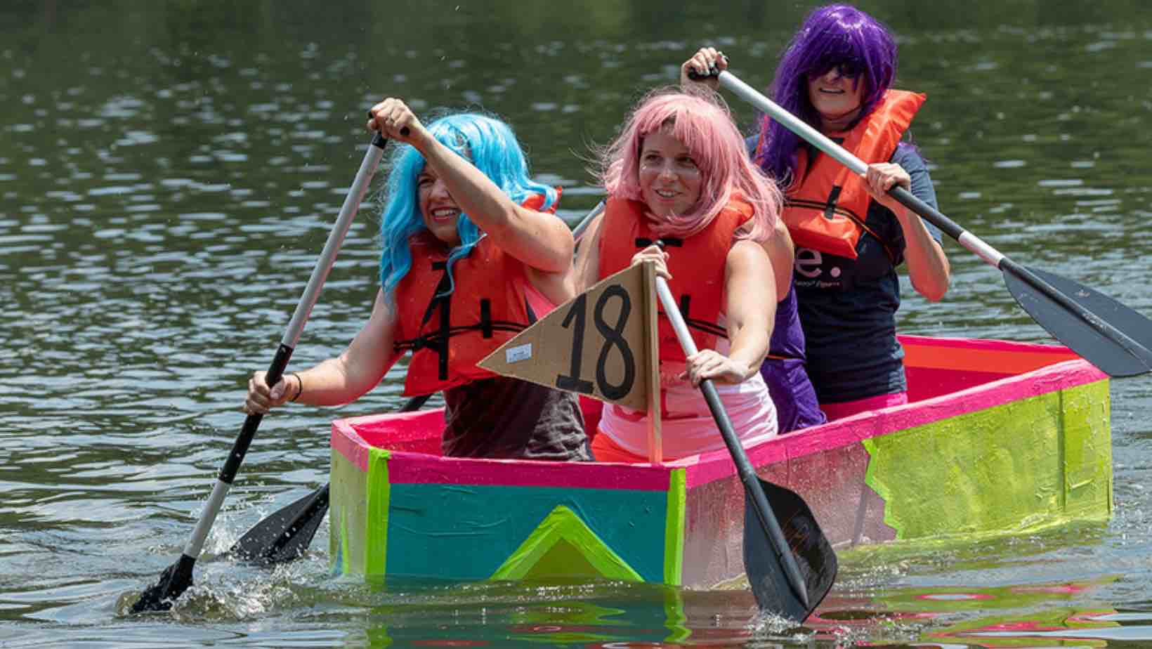 Girls with colorful wigs in a carboard boat